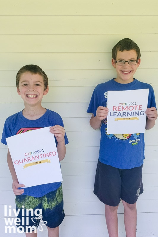 mom and son holding back to school printable signs