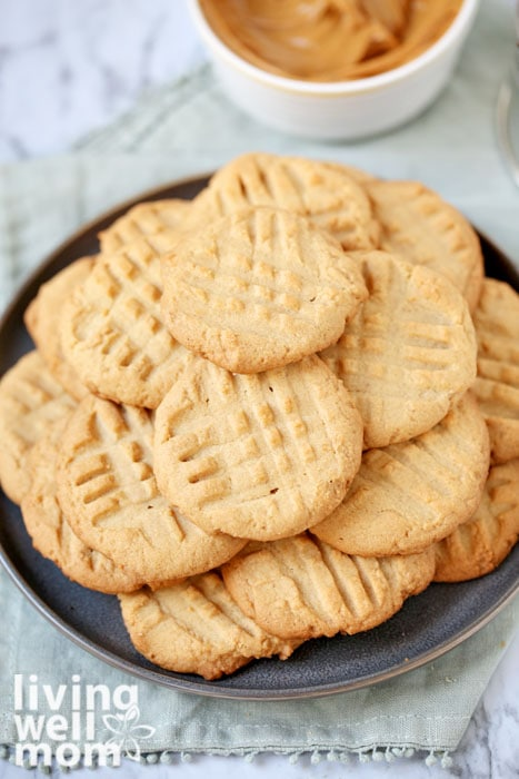 Pile of gluten free peanut butter cookies with bowl of peanut butter in the background.