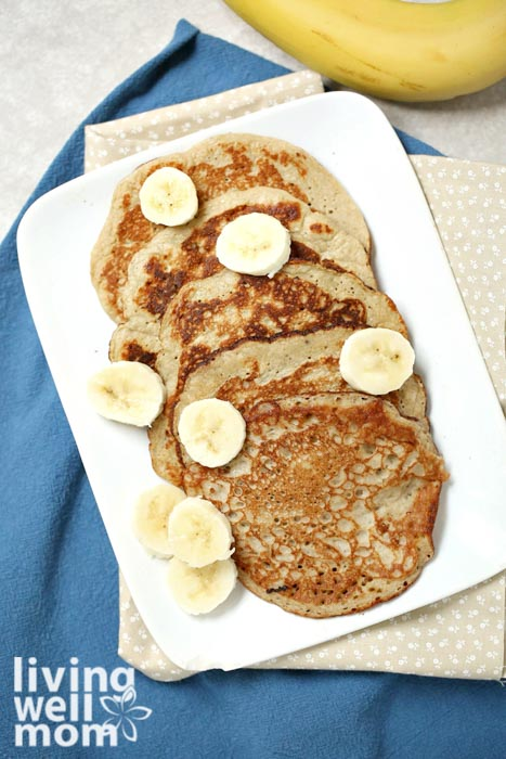 Banana egg pancakes cooked and topped with sliced bananas.