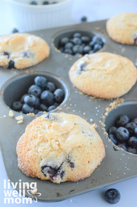 blueberry muffins in a tin with blueberries in the empty slots
