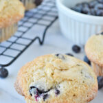 blueberry muffins cooling on a rack with a ramekin of blueberries