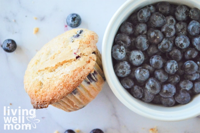 blueberry muffin sitting next to a bowl of fresh blueberries