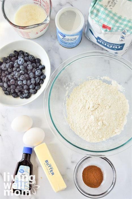 ingredients for gluten-free blueberry muffins - milk, salted butter, white granulated sugar, eggs, vanilla extract, baking powder, salt, cinnamon, nutmeg, flour, fresh blueberries