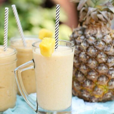 Mango pineapple smoothie divided into 3 cups with straws