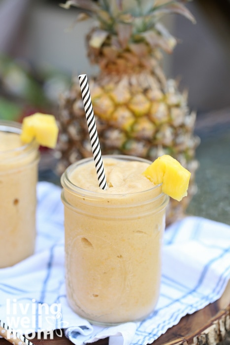 Mango pineapple smoothie poured into a mason jar with pineapple wedge on top