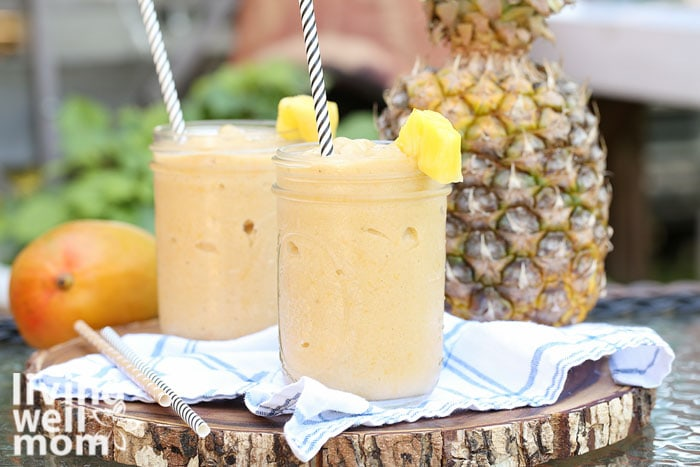 2 mango pineapple smoothies on a wood round