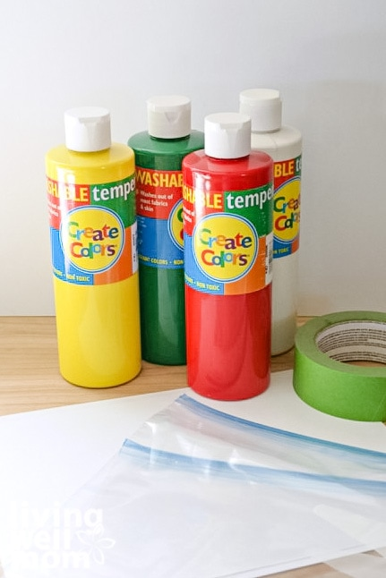 Bottles of finger paint, with paper, ziplock bags and painters tape on a table.
