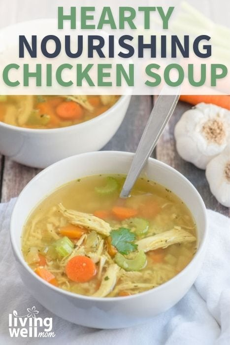 bowl of hearty nourishing chicken soup in a white bowl on white napkin with garlic and carrots
