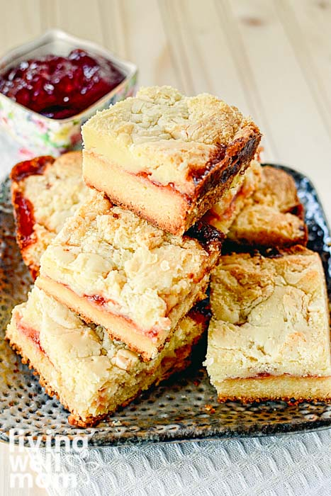 pile of white chocolate raspberry bars with raspberry jam in background