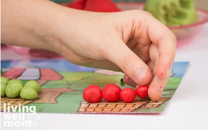 A person placing playdough apples into a basket on an activity mat.