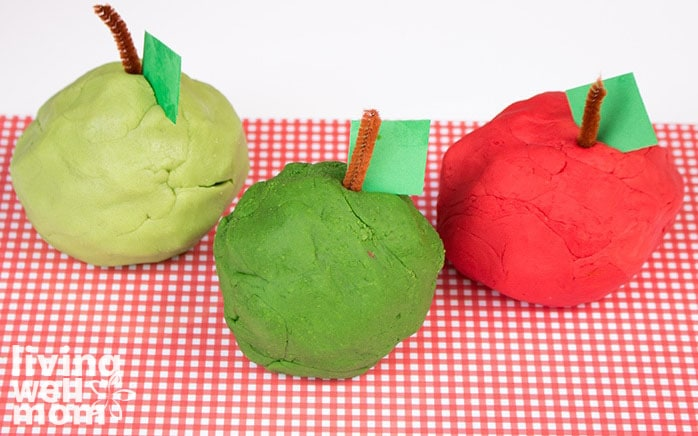Large balls of red and green playdough apples, with a construction paper leaf and pipecleaner stem.