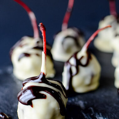 Cherries covered in white chocolate with a dark chocolate drizzle