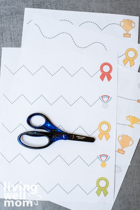 A fair of black and blue Fiskars brand scissors for kids, on a printed cutting practice sheet.