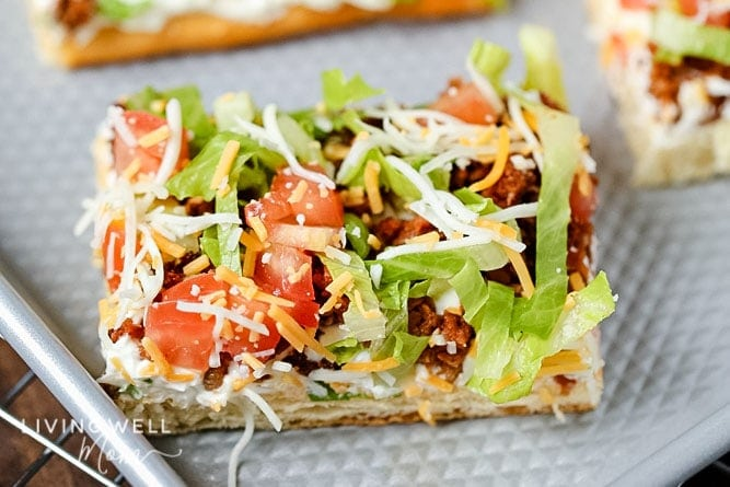 Slice of taco pizza with lettuce and tomato on top