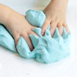 child's hands squishing homemade fluffy blue slime