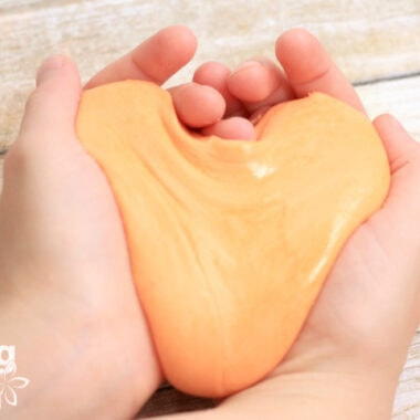 homemade orange silly putty in child's hands
