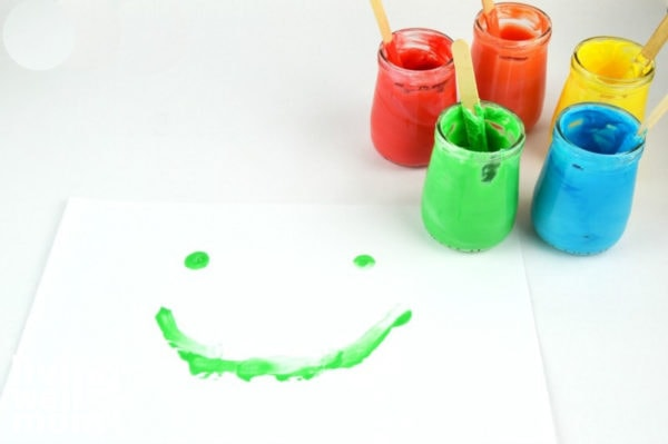jars of edible finger paint with a green smiley face painted on