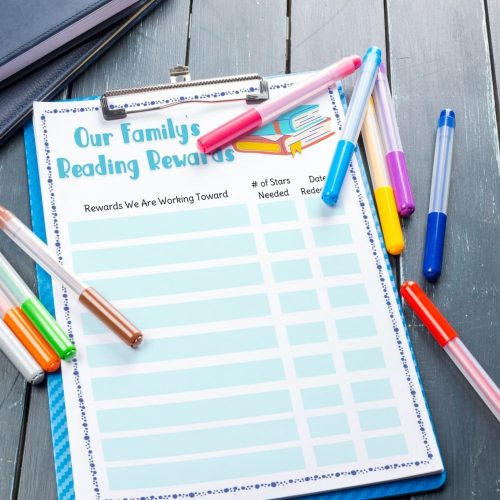our family's reading rewards printable chart on blue clipboard with markers