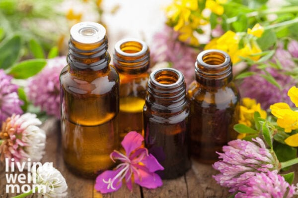 Essential oils for dry skin all gathered together on a table with botanicals..