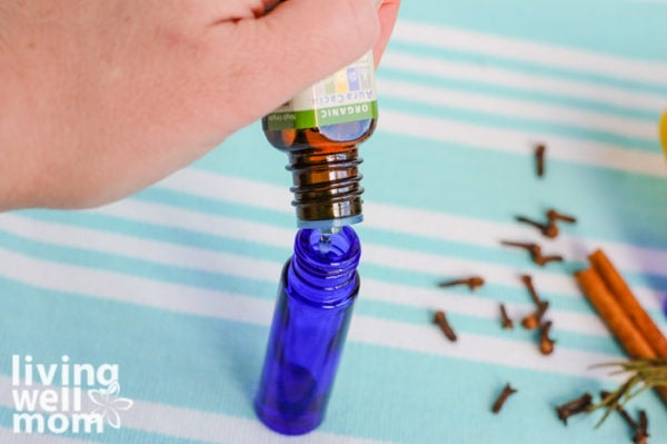 woman adding essential oil to a roller bottle