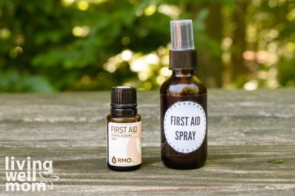 brown glass spray bottle first aid spray and essential oil with a bandage on wood with woods background