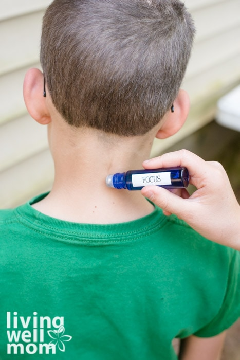 rolling an essential oil blend on a child's neck