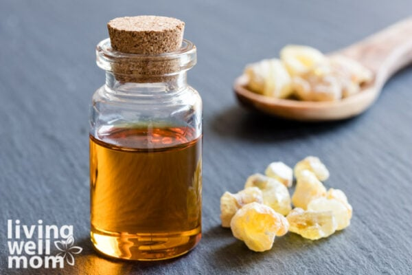 frankincense in a wooden spoon next to a bottle of essential oil