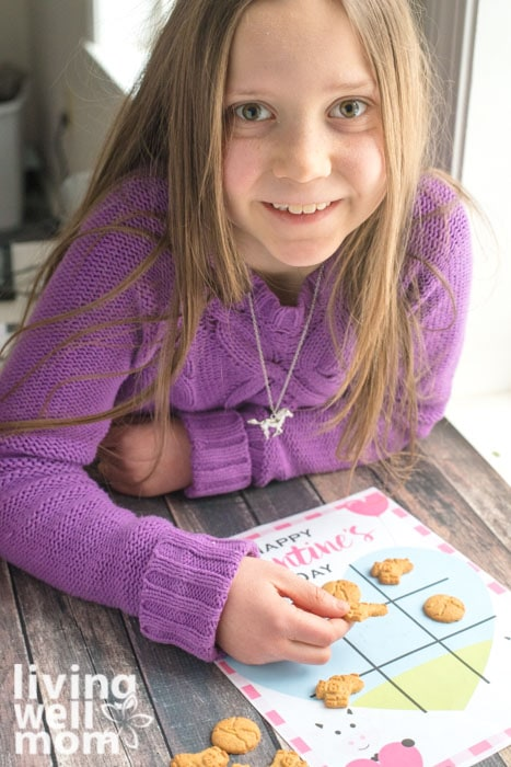 Young girl in purple sweater playing a Valentine's Day tic tack toe game with cookies.