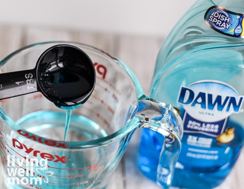 adding dawn dish soap to glass measuring cup - shower cleaner recipe