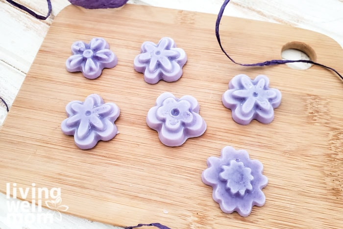 Assorted flower shaped DIY lotion bars displayed on a wooden board.