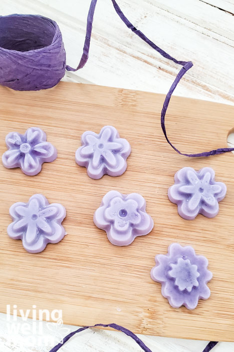 Purple, flower-shaped lotion bars made with essential oils.