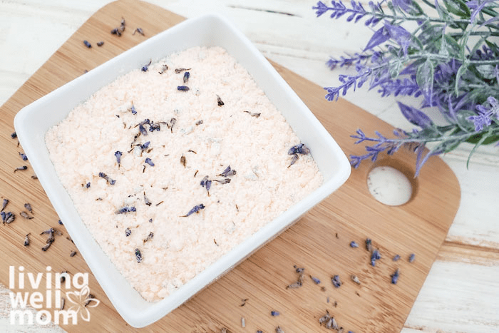 DIY bath soak on a cutting board atop of a surface, with a bouquet of lavender to the side.