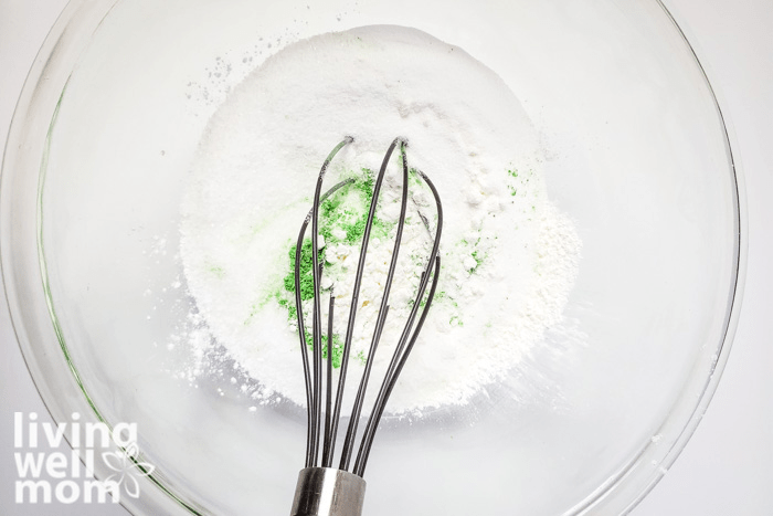 Green mica powder being whisked into homemade fizzy salt mixture.