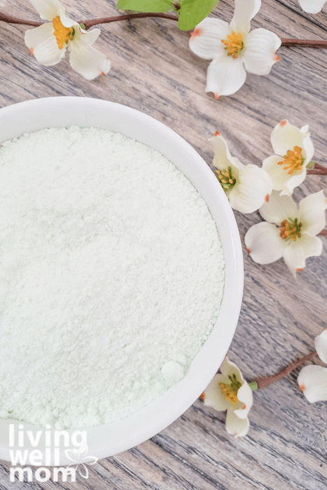 Scented homemade bath salts in a white bowl next to faux flowers.