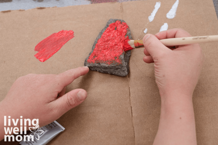 A child painting a small rock with red acrylic paint.