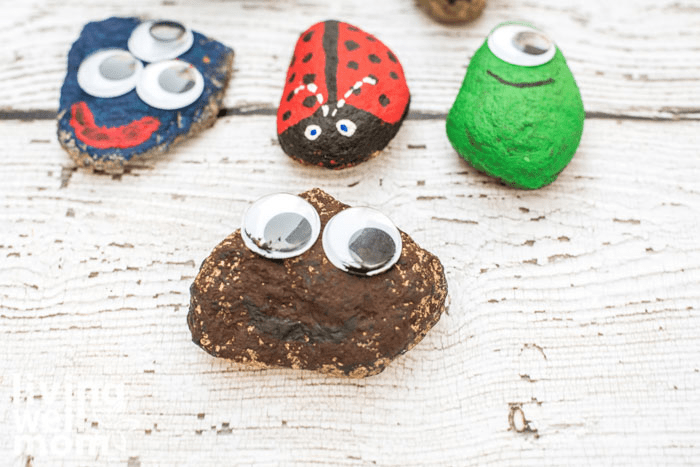 4 painted pet rocks on a table, with googly eyes attached.