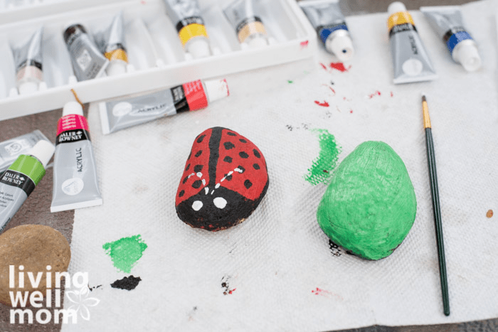 Paper towels on a surface, with acrylic paints and paintbrushes ready for a painted rock craft.