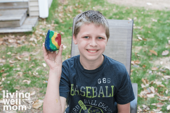 A boy holding up a rainbow designed pet rock he painted with a smile on his face.