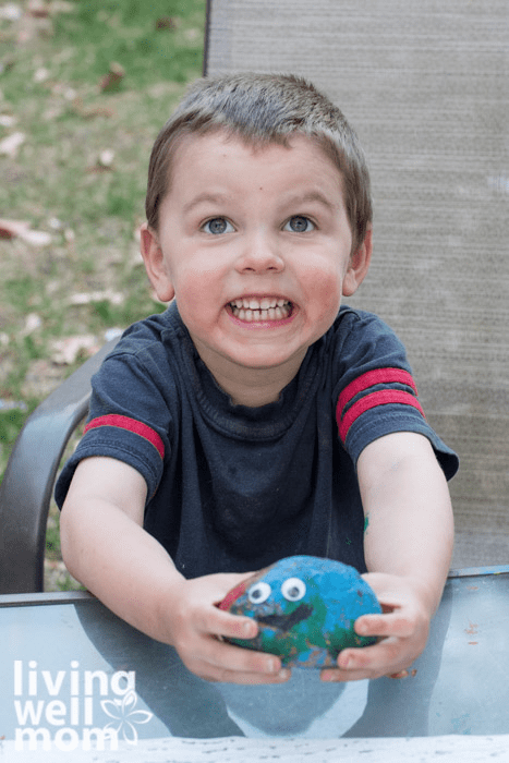 A boy proudly showing his pet rock painted with blue, green and red acrylics.