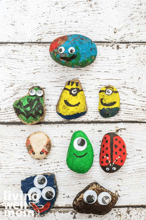 Pet rocks on a wooden table, with painted monsters, animals and minions.