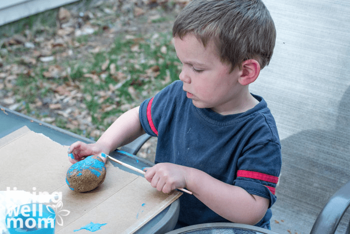 A young boy covering a round rock with bright blue paint.