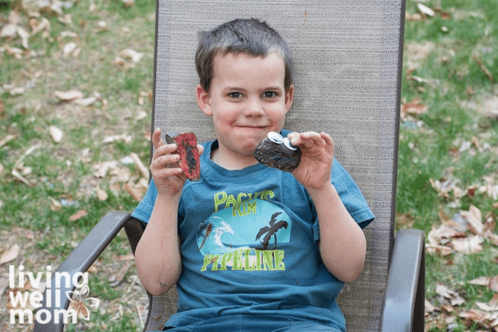 A child sitting in a chair holding two pet rocks.
