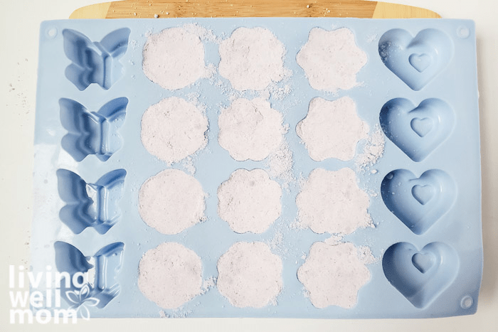 A silicone tray filled with moistened mixture for homemade bath bombs.