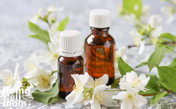 2 bottles of essential oil amongst jasmine flowers