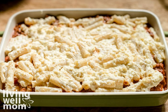 layered cheesy pasta on top of meat sauce for baked ziti