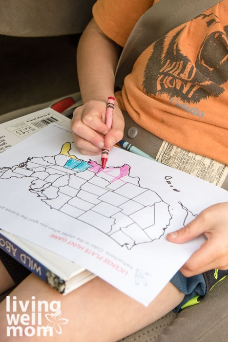 Child coloring a US map on a road trip