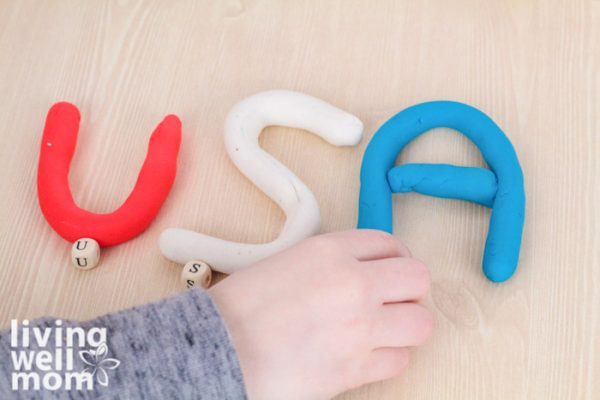 Child spelling USA with red, white, and blue playdough