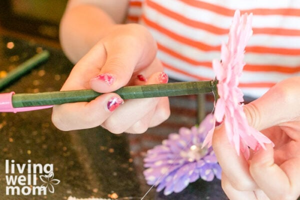 Child attaching a flower to a pen
