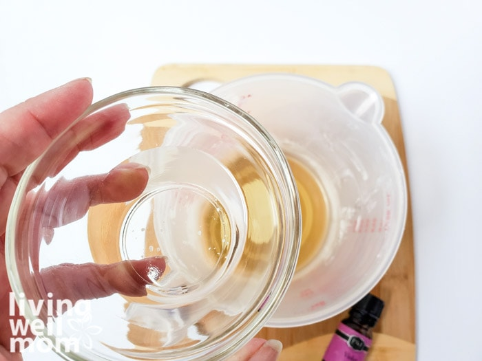 A small bowl of almond oil about to be poured into a measuring cup of homemade lotion bar ingredients.