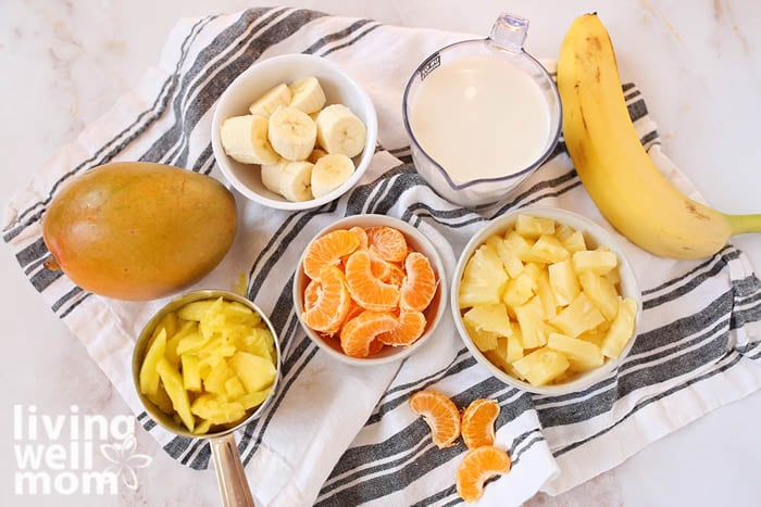 Ingredients for a mango pineapple smoothie in individual bowls